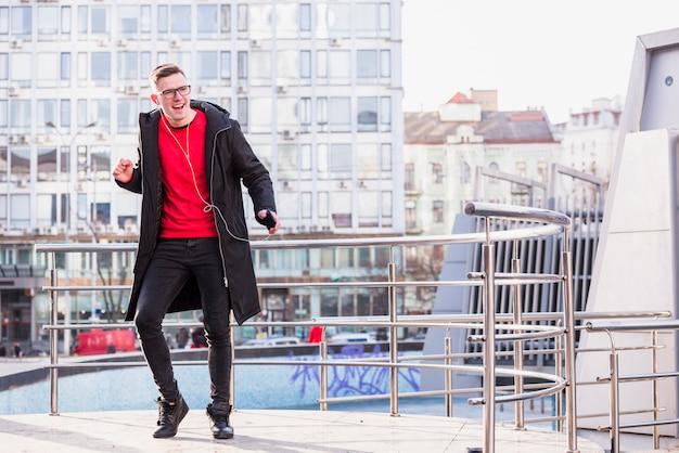 Stijlvolle jonge man luisteren muziek op oortelefoon dansen in de open lucht