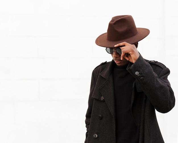 Stijlvolle jonge man met bril en hoed