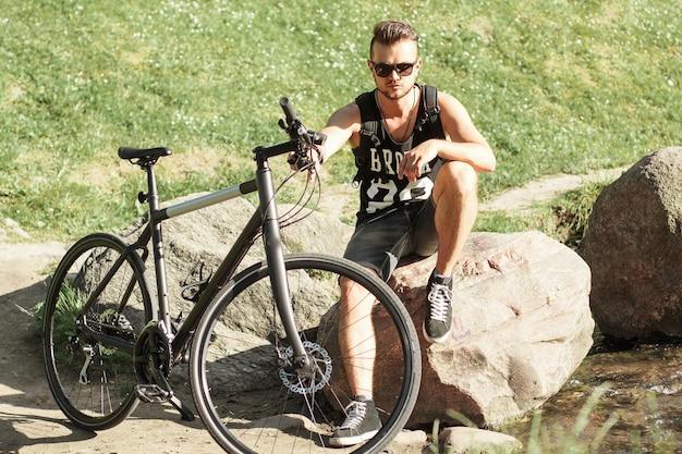 Stijlvolle jonge man met een fiets