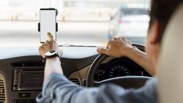 Stijlvolle jonge man met een lege scherm mobiele telefoon in de auto