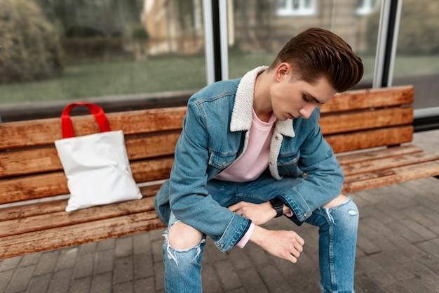 Stijlvolle jonge man met kapsel in vintage casual spijkerbroek kleding met trendy stoffen tas zit op houten bankje bij een bushalte in de stad. cool knappe jongen in modieuze denim jeugdkleren op straat.
