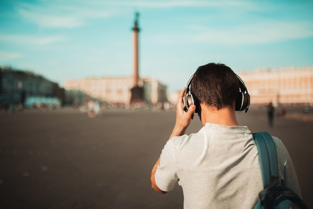 Stijlvolle jonge man met rugzak en draadloze koptelefoon buiten