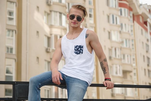 Stijlvolle jonge man met tatoeages en trendy kapsel