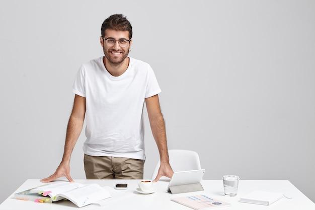 Stijlvolle jonge man permanent in de buurt van bureau