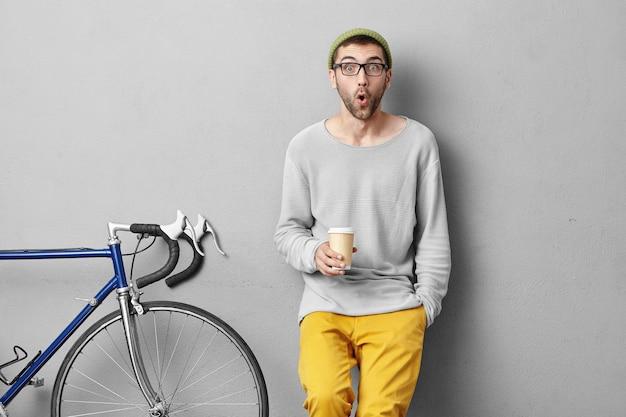 Stijlvolle jonge man permanent in de buurt van fiets