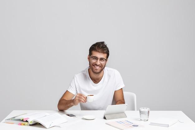 Stijlvolle jonge man zit aan bureau