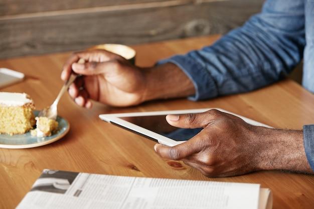Stijlvolle jonge man zit in café met tablet