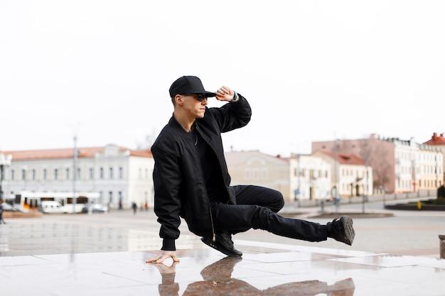 Stijlvolle jonge mannelijke danser in modieuze zwarte kleding blake dans dansen op een straat in de stad op een herfstmiddag. levensstijl.