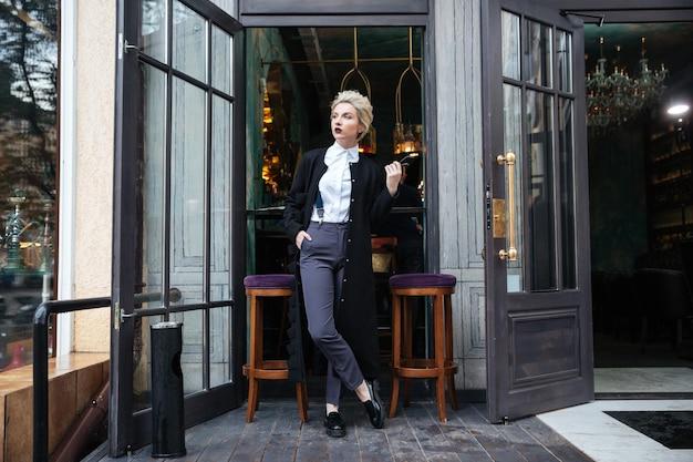 Stijlvolle jonge modeblogger die zich voordeed in café