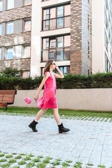 Stijlvolle jonge modelvrouw in een roze jurk loopt op de achtergrond van de stadsstraat in modieuze mooie kleding