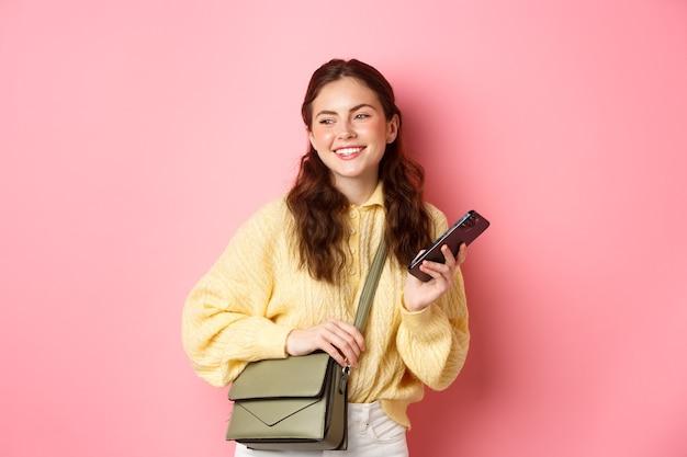 Stijlvolle jonge moderne vrouw die ergens heen gaat met smartphone en haar tas, opzij kijkend met een gelukkige glimlach, staande tegen een roze muur