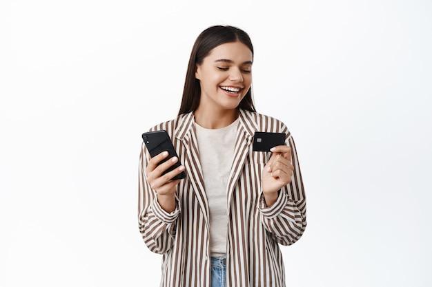Stijlvolle jonge moderne vrouw lacht, kijkt naar plastic creditcard, betaalt online met mobiele telefoon, winkelt in smartphone-app, witte muur