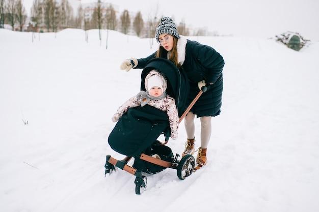 Stijlvolle jonge moeder brengt tijd door met haar dochter in wandelwagen in winter park