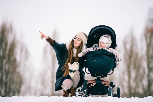 Stijlvolle jonge moeder die met haar dochter in wandelwagen in sneeuw de winterpark communiceert.