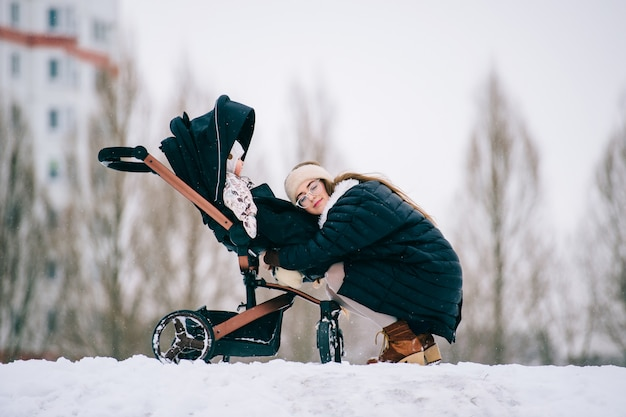 Stijlvolle jonge moeder hugs haar dochter zit in de wandelwagen in park buiten in de winter.