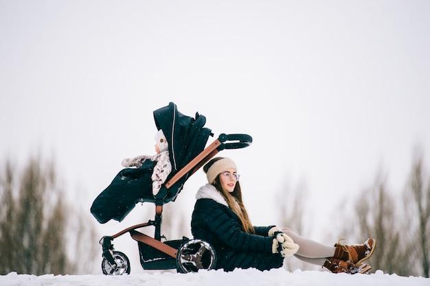 Stijlvolle jonge moeder rusten met haar dochter zitten in de wandelwagen in het park buiten in de winter.