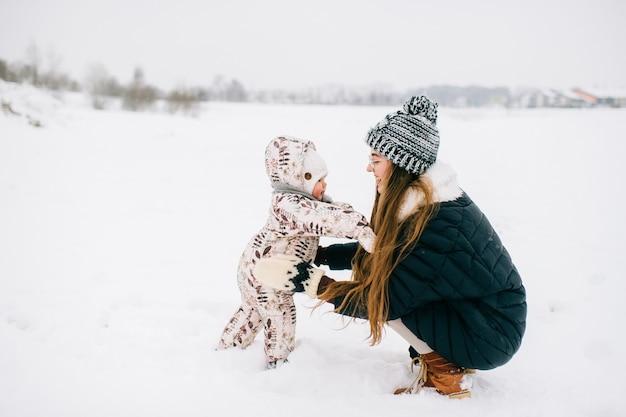 Stijlvolle jonge moeder spelen met dochtertje buiten in de winter.