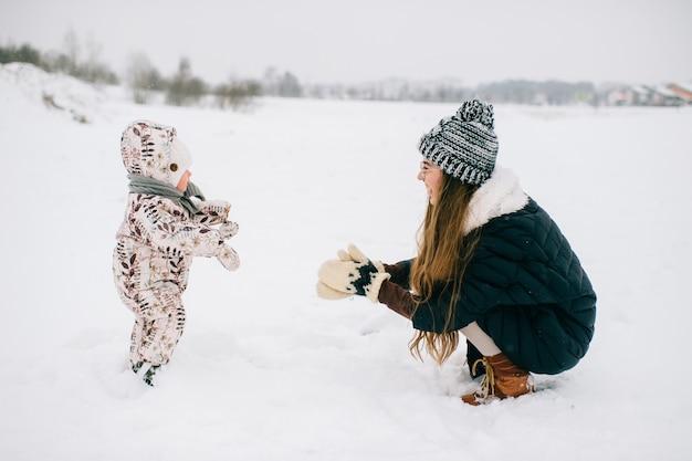 Stijlvolle jonge moeder spelen met kleine baby op natuur in de winter