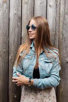 Stijlvolle jonge mooie slavische meid in vintage zonnebrillen in denim kleding met skory staat in de buurt van een oude houten muur