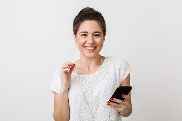 Stijlvolle jonge mooie vrouw glimlachend in t-shirt aan, luisteren naar muziek in oortelefoons, smartphone vasthouden, apparaat gebruiken, geïsoleerd, gelukkig, positief gebaar