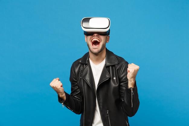 Stijlvolle jonge ongeschoren man in zwarte jas wit t-shirt op zoek in headset, virtual reality vr geïsoleerd op blauwe muur achtergrond studio portret. mensen emoties levensstijl concept. bespotten kopie ruimte.