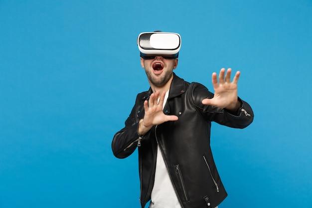 Stijlvolle jonge ongeschoren man in zwarte jas wit t-shirt op zoek in headset, virtual vr reality geïsoleerd op blauwe muur achtergrond studio portret. mensen emoties levensstijl concept. bespotten kopie ruimte.