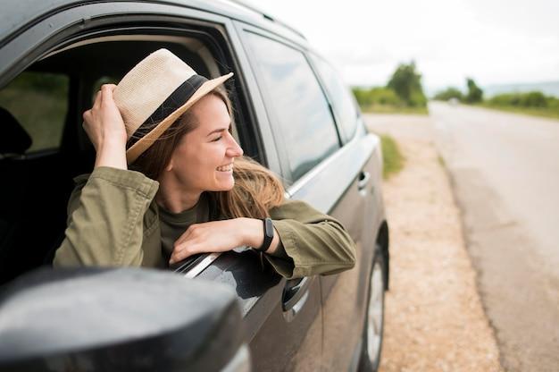 Stijlvolle jonge reiziger genieten van rit met auto