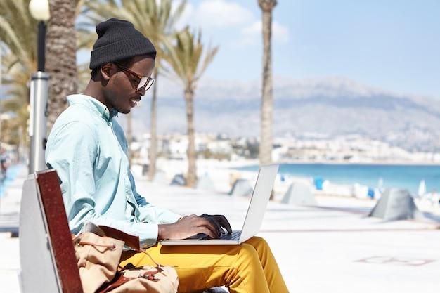 Stijlvolle jonge schrijver in hoed en tinten typen op keyborad op laptop