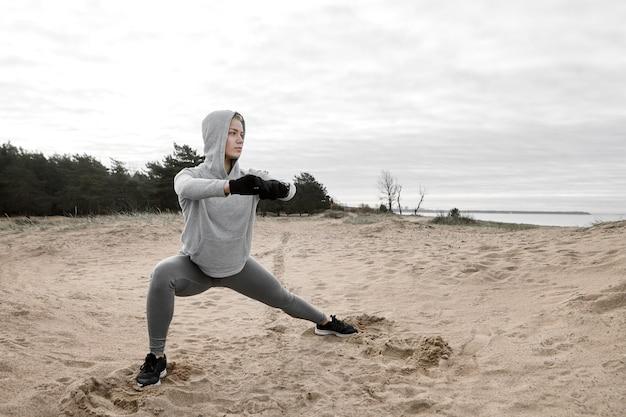 Stijlvolle jonge sportvrouw met handschoenen, hoodie en sneakers staande yoga pose voor sterke benen, spieren voorbereiden op cardiotraining. zelfverzekerd atletische vrouw in kap uitoefenen op strand
