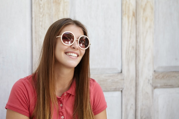 Stijlvolle jonge studente in poloshirt en ronde zonnebril met gelukkige en geïnspireerde uitdrukking, zijwaarts kijkend en glimlachend, droomend van zomervakantie. mensen