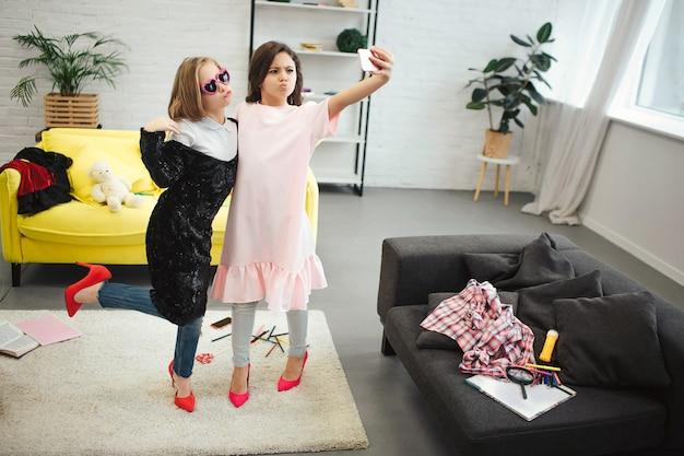 Stijlvolle jonge tieners staan in de kamer en poseren op telefooncamera. ze dragen kleding voor volwassen vrouwen. brunette houd camera. ze nemen selfie.