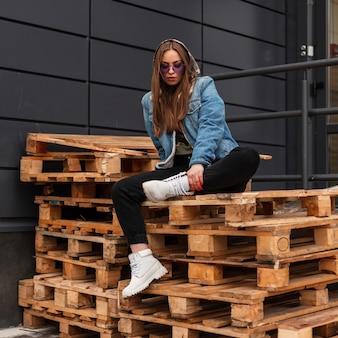 Stijlvolle jonge vrij cool hipster vrouw in trendy jeans kleding in violet modieuze bril in lederen witte laarzen zittend op houten pallets in de buurt van muur in de straat. stedelijke mooi meisje. casual stijl