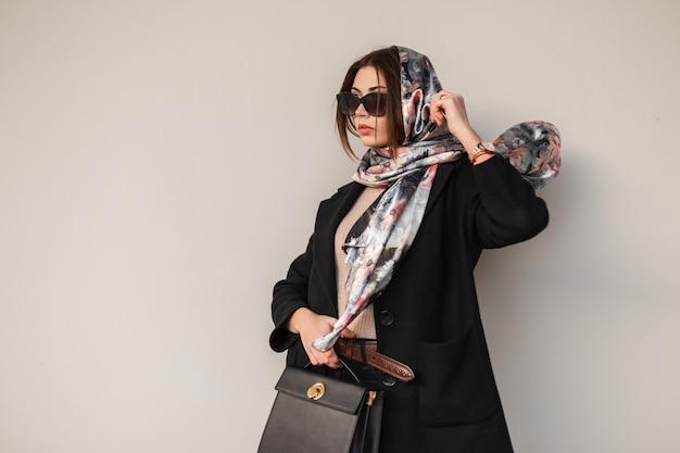 Stijlvolle jonge vrouw bedrijfsmodel met een elegante sjaal op hoofd in modieuze zonnebril in een trendy jas met lederen zwarte handtas staat in de buurt van een vintage muur. moderne luxe meisje. sensuele dame.