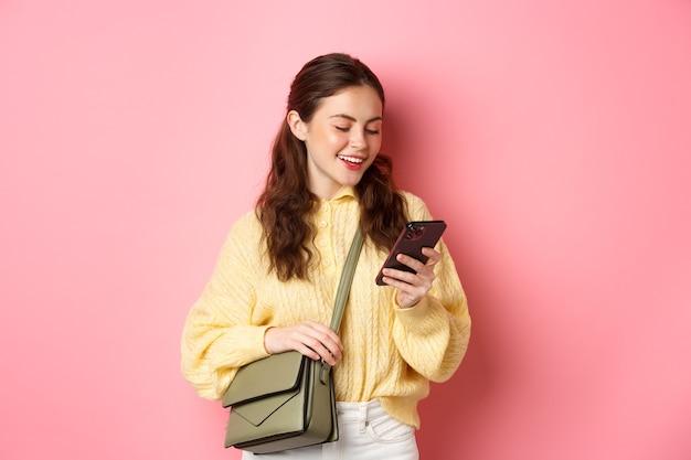 Stijlvolle jonge vrouw chatten op haar telefoon, staande met tas, smartphone-scherm lezen, messaging, staande over roze muur
