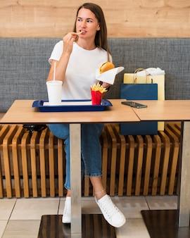 Stijlvolle jonge vrouw die snel voedsel eet