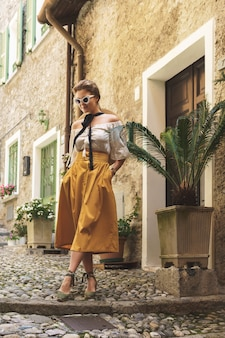 Stijlvolle jonge vrouw die zich voordeed in de straten van de kleine italiaanse stad