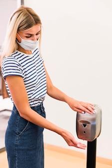 Stijlvolle jonge vrouw handen desinfecteren
