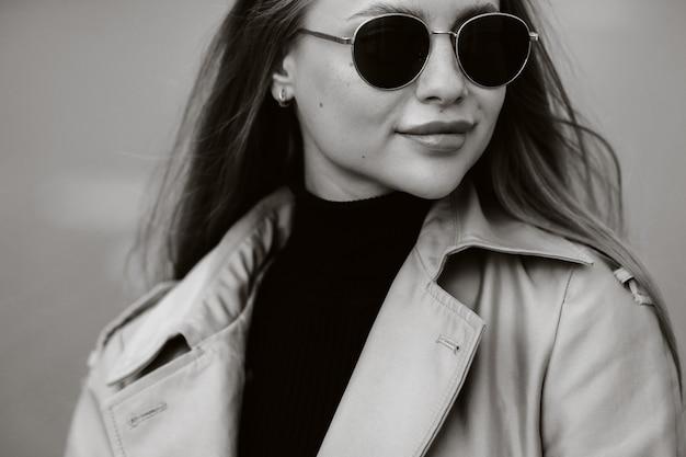 Stijlvolle jonge vrouw in een beige jas en bril op een straat in de stad. street fashion voor dames. herfstkleding. stedelijke stijl.