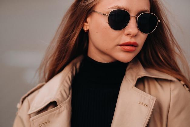 Stijlvolle jonge vrouw in een beige jas en bril op een straat in de stad