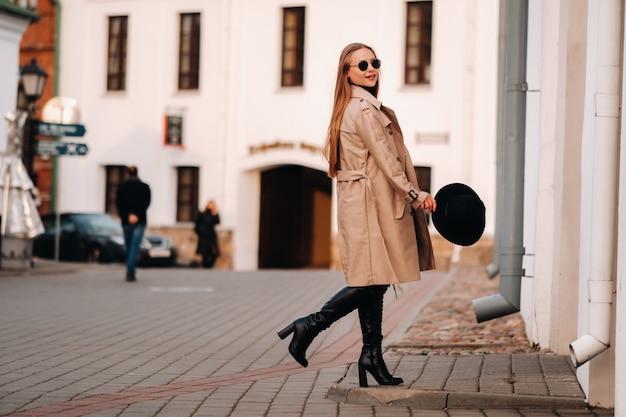 Stijlvolle jonge vrouw in een beige jas en een zwarte hoed in zijn handen en bril op een straat in de stad. street fashion voor dames. herfstkleding. stedelijke stijl.