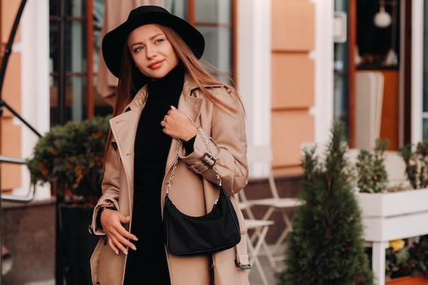 Stijlvolle jonge vrouw in een beige jas en zwarte hoed en met een zwarte tas op een straat in de stad. street fashion voor dames. herfstkleding. stedelijke stijl.
