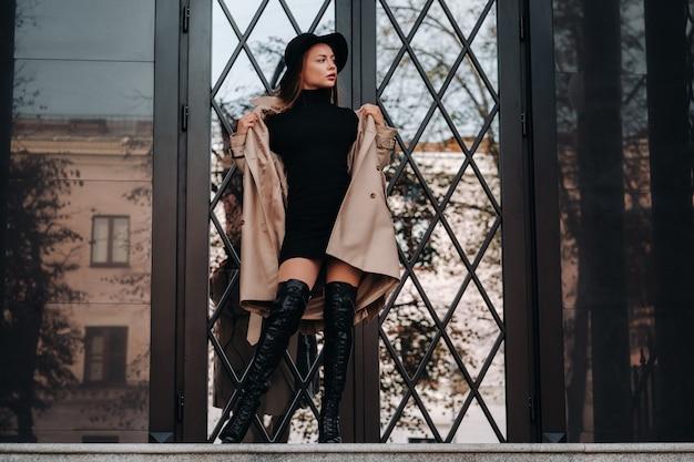 Stijlvolle jonge vrouw in een beige jas in een zwarte hoed op een straat in de stad. street fashion voor dames. herfstkleding. stedelijke stijl.