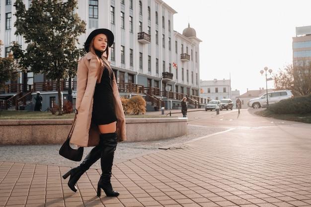 Stijlvolle jonge vrouw in een beige jas in een zwarte hoed op een straat in de stad. street fashion voor dames.