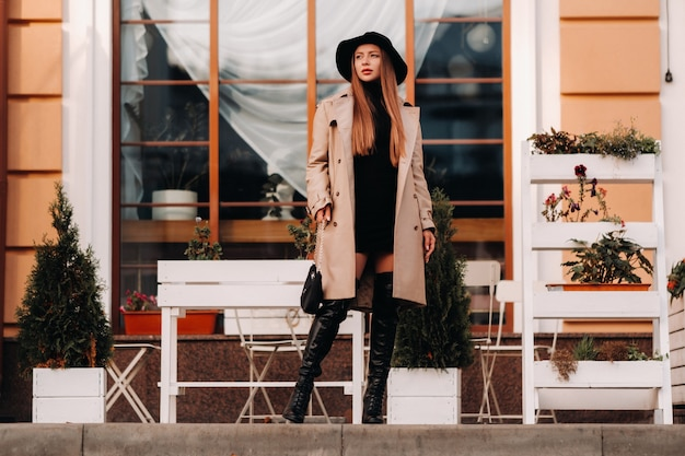Stijlvolle jonge vrouw in een beige jas in een zwarte hoed op een straat in de stad.