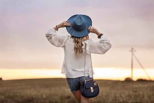 Stijlvolle jonge vrouw in een hoed kijkt naar de zonsondergang