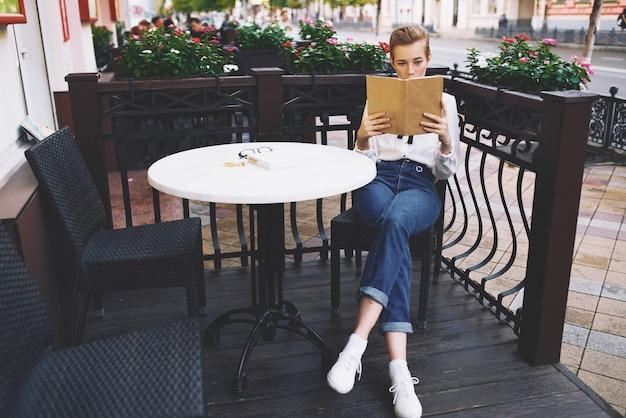 Stijlvolle jonge vrouw in een shirt met een boek in haar handen zit in de zomer aan een tafel in een café
