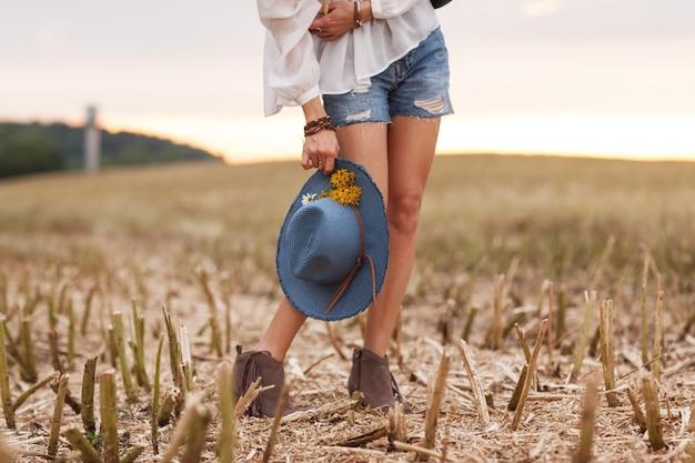 Stijlvolle jonge vrouw in een veld met bloemen van etnische stijl