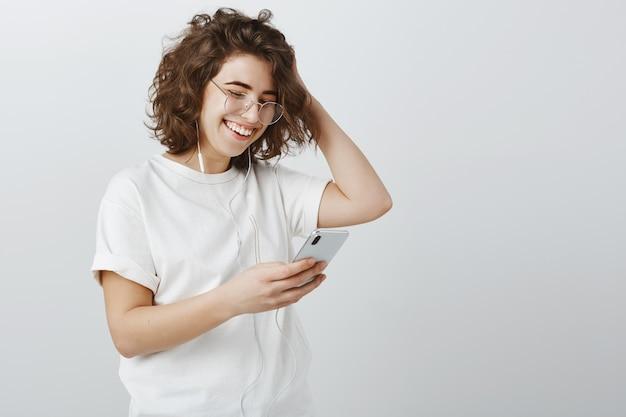 Stijlvolle jonge vrouw in glazen afspeellijst maken in telefoon, muziek luisteren via koptelefoon