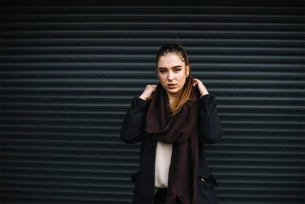 Stijlvolle jonge vrouw in jas met sjaal in de buurt van muur van geprofileerde platen