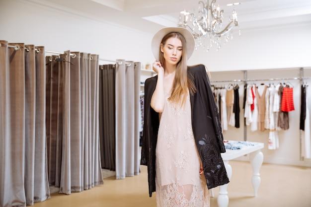 Stijlvolle jonge vrouw in jurk, jas en hoed die zich in de showroom bevindt